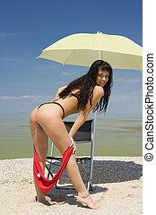 hot beach. - Beautiful topless Brunette on a hot beach.