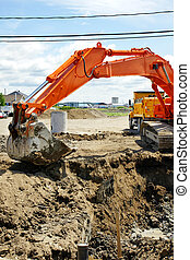 Orange mechanical digger and hole - Construction: Bright...