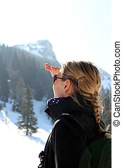 Woman looking up on a mountain in winter