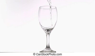 White wine poured in super slow motion in a glass against...