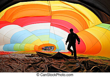 Man inflating a hot air balloon - Man inside a colorful hot...