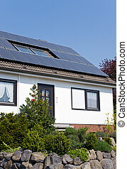 White house with solar panels - Solar panels on the roof of...