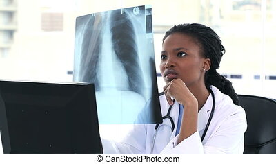 Doctor looking to a chest X-ray while sitting at her desk