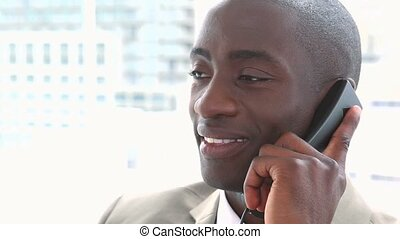 Black businessman smiling on the phone sitting in a office