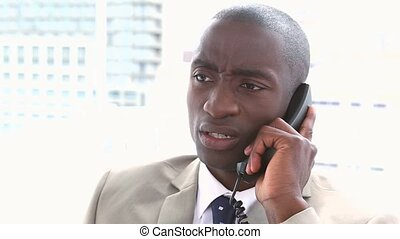Businessman receiving a bad news by phone in a office