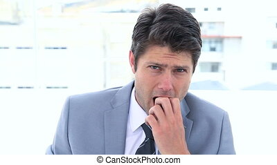 Businessman biting his nails against white background
