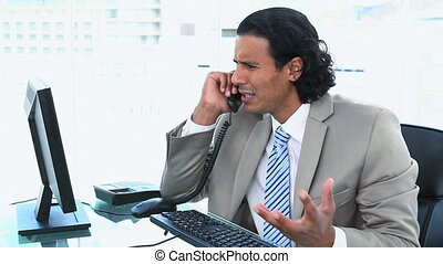 Businessman having trouble while phoning