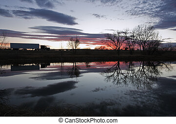 Semi Truck seen during sunset - reflected in the pond