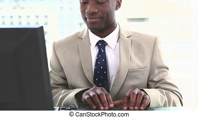 Smiling businessman typing on a keyboard