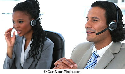 Smiling people speaking with headset in an office