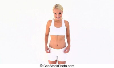 Blonde shrugging her shoulders after touching her skinny belly