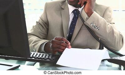 Black businessman working while phoning