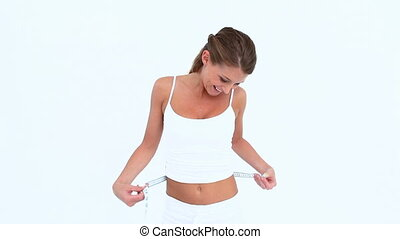 Smiling woman using a tape to measure her waist against...