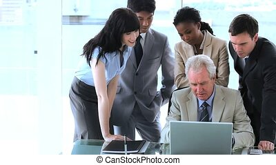 Businesswoman pointing at a laptop in a bright room