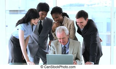 Smiling employees surrounding their manager in a bright room