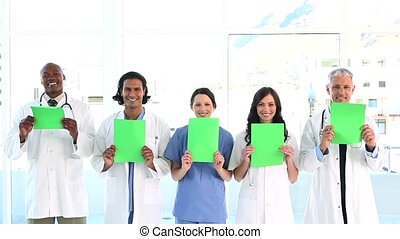 Smiling medical team showing blank papers in a bright room