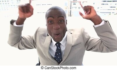 Black businessman very happy sitting in his office