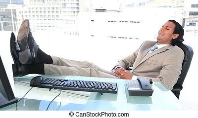 Latin businessman resting in his office with a city view