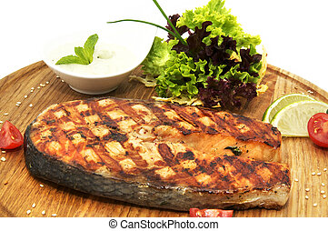 salmon steak cooking on a grill in the restaurant