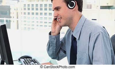 Businessman working with a computer and a headset in a...
