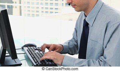 Businessman typing on a keyboard and wearing headset