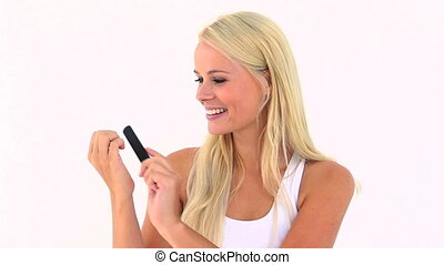 Smiling blonde lifting her nails against white background