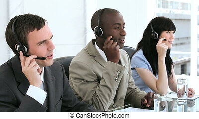 Smiling call centre agents working with headsets in a bright...