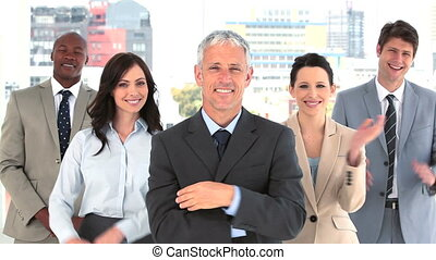 Happy businessman applauding while standing in a bright room