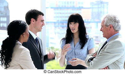 Business people standing white talking together in a bright...