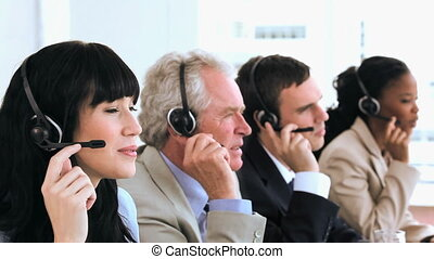 Joyful call centre agents sitting while wearing headsets in...