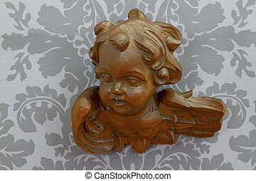 Carved wooden angel on gray paperhangings