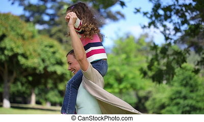 Woman turning with her daughter on her shoulders in a park