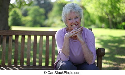 Retired woman smiling while sitting on a bench in a park