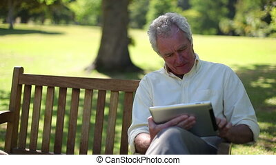 Retired man using an ebook while sitting on a park bench