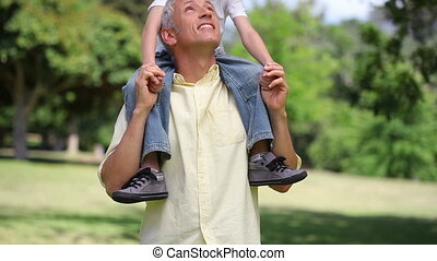 Man holding a little boy on his shoulders