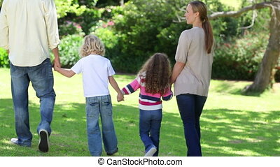 Family walking hand in hand in a park