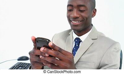 Black businessman texting on a smartphone in his office