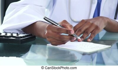Black doctor writing a note in an office