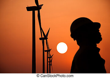 The Silhouette of windmills worker with sunset