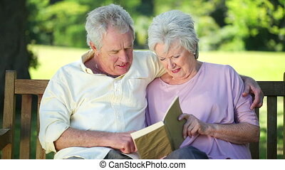 Retired couple reading a book together while sitting on a...