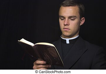Priest with Prayer book - Young Priest in black reading...