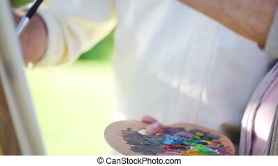 Mature couple painting together in a park