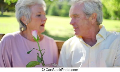Mature woman smelling a rose while sitting with her husband...