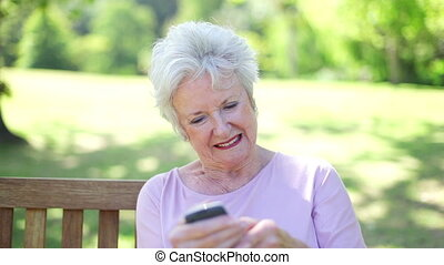 Retired woman using a mobile phone sitting in a park