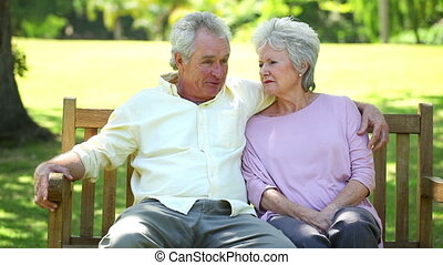 Retired couple sitting on a bench in a park