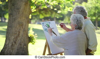Retired people painting a tree together in a park
