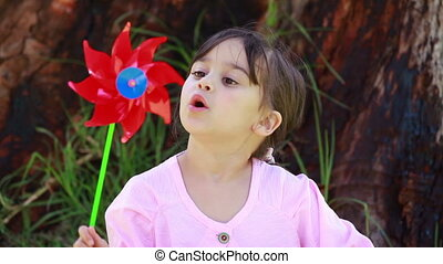 Happy little girl blowing on a pinwheel in the countryside