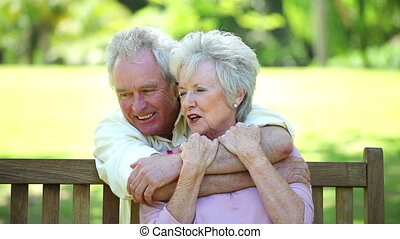 Retired man embracing his wife in a park