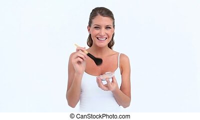 Laughing woman applying blush on her face against white...