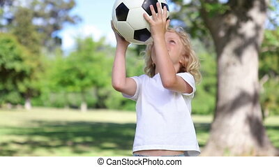 A little boy playing with a football